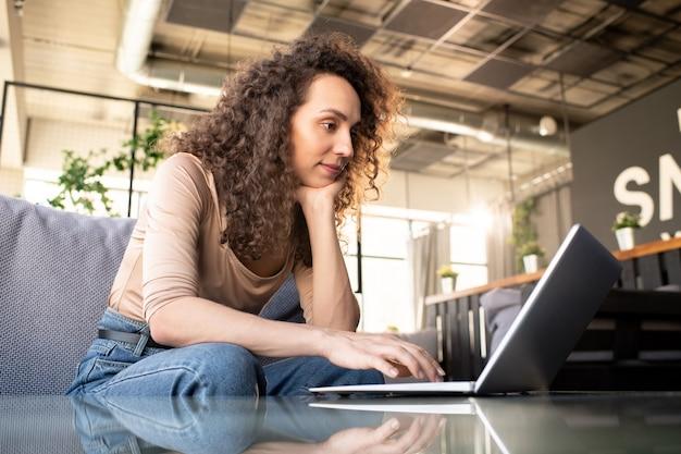 Jolie femme d'affaires en tenue décontractée en regardant l'écran de l'ordinateur portable alors qu'il était assis sur le canapé au café