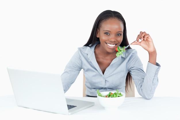 Jolie femme d'affaires travaillant avec un cahier tout en mangeant une salade