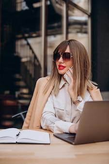 Jolie femme d'affaires travaillant sur ordinateur dans un café