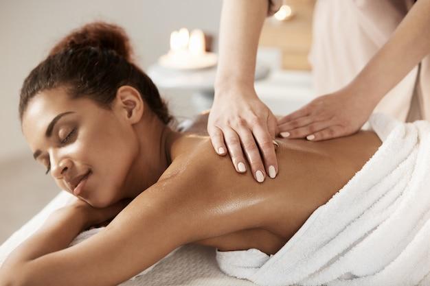 Jolie femme africaine ayant massage relaxant dans le salon spa. yeux fermés.