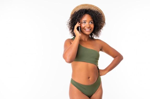 Jolie femme africaine se tient en maillot de bain, parler au téléphone avec des amis ou en famille et sourit isolé sur blanc