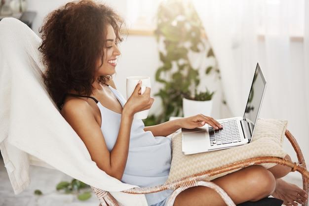 Jolie femme africaine souriante tenant la tasse en regardant un ordinateur portable assis sur une chaise à la maison.