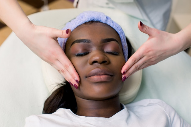 Jolie femme afro-américaine bénéficiant d'un massage du visage au salon de beauté, vue de dessus, espace copie