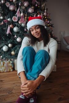 Jolie femme afro-américaine est assise près d'un arbre de noël, posant à la caméra