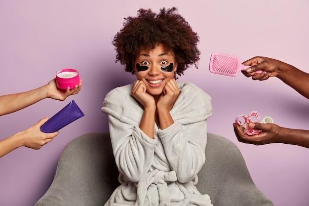 Jolie femme afro-américaine joyeuse avec des patchs d'hydrogel sous les yeux pour réduire les macareux