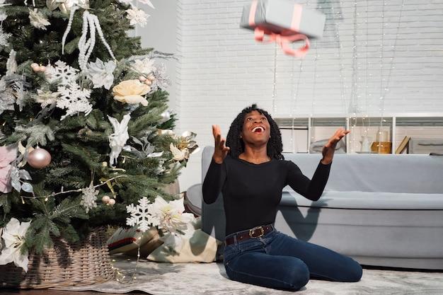 Jolie femme afro-américaine s'assoit près d'un arbre de noël