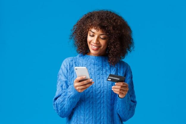 Jolie femme afro-américaine souriante, payant pour l'achat en ligne