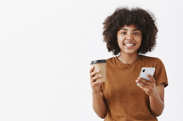 Jolie femme afro-américaine urbaine à l'allure amicale avec une coiffure afro tenant une tasse de papier avec du café ou du thé et un smartphone à la main souriant largement en lisant les nouvelles le matin