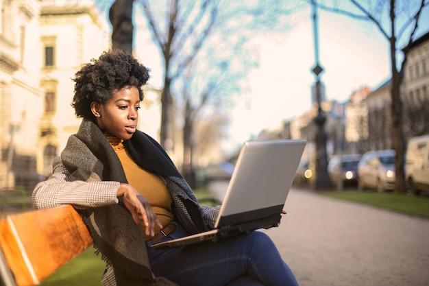 Jolie femme afro assise sur un banc avec un ordinateur portable