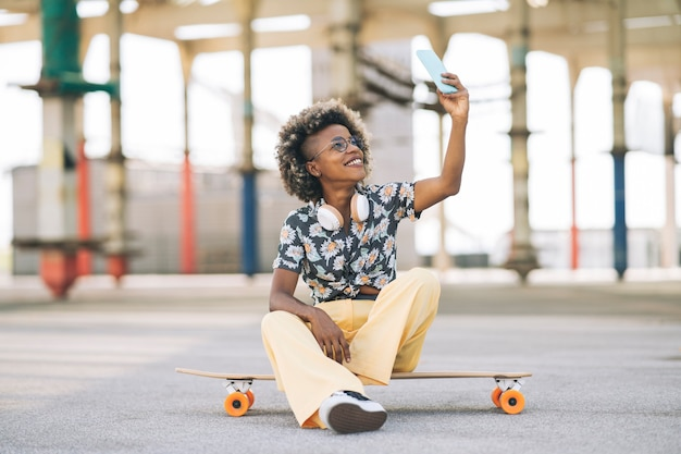 Jolie femme afro blonde dans des verres avec planche à roulettes, assise prend une photo avec un smartphone