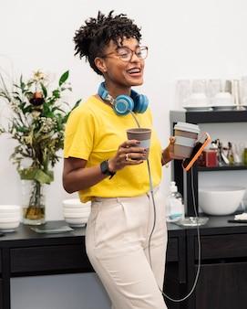 Jolie femme afro en coworking avec casque et café
