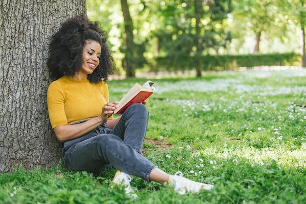 Jolie femme afro lisant un livre dans un jardin. mise au point sélective.