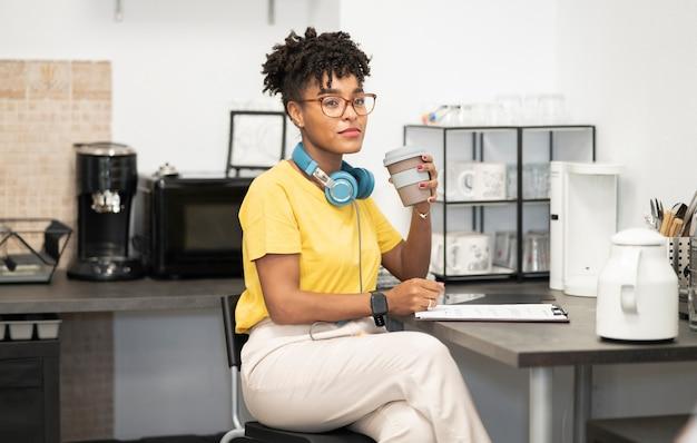 Jolie femme afro avec des lunettes au bureau buvant du café