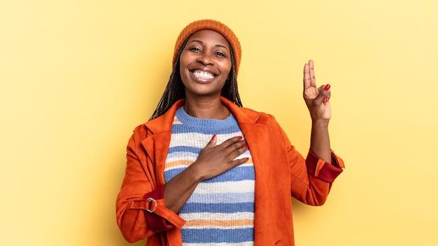 Jolie femme afro noire ayant l'air heureuse, confiante et digne de confiance, souriante et montrant le signe de la victoire, avec une attitude positive