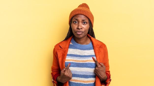 Jolie femme afro noire pointant vers elle-même avec un regard confus et interrogateur, choquée et surprise d'être choisie