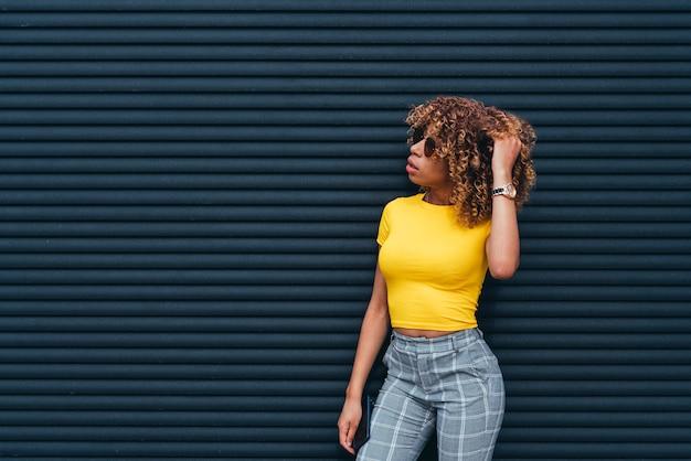 Jolie femme avec afro posant dans la rue