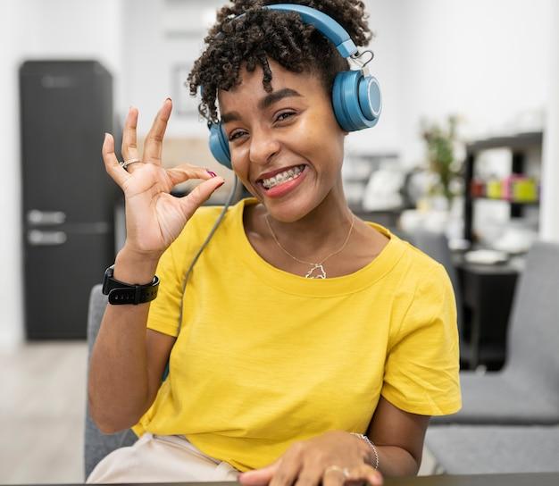 Jolie femme afro travaillant en coworking avec des écouteurs avec un geste correct