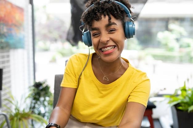 Jolie femme afro travaillant en coworking avec des écouteurs