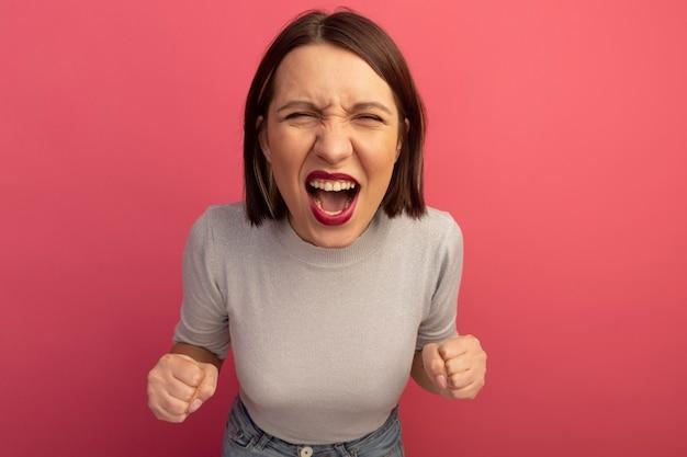 Jolie femme agacée garde les poings et les cris isolés sur le mur rose