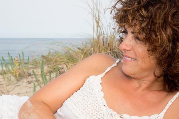 Jolie femme d'âge moyen allongée le long du bord de mer