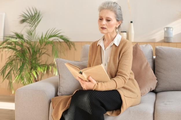 Jolie femme d'âge moyen appréciant la lecture d'un livre assis sur le canapé dans son salon en souriant pendant qu'elle lisait.