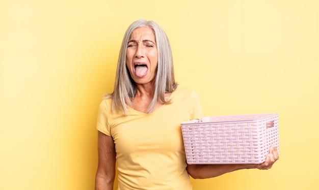 Jolie femme d'âge moyen avec une attitude joyeuse et rebelle, plaisantant et tirant la langue. concept de panier vide