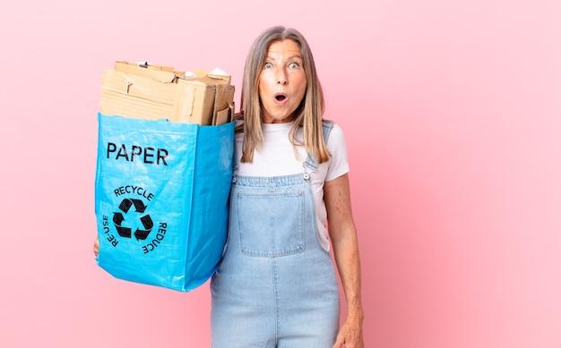 Jolie femme d'âge moyen ayant l'air très choquée ou surprise du concept de carton de recyclage