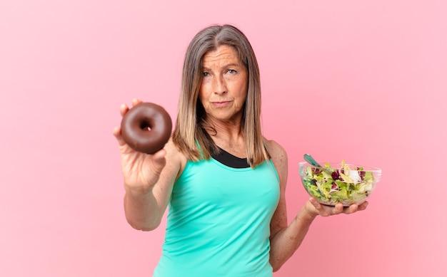 Jolie femme d'âge moyen coparing une salade et un beignet