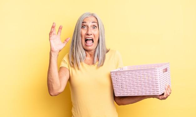 Jolie femme d'âge moyen criant avec les mains en l'air. concept de panier vide