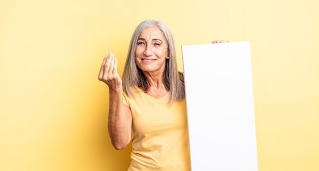 Jolie femme d'âge moyen faisant un geste de capice ou d'argent, vous disant de payer. concept de toile vide