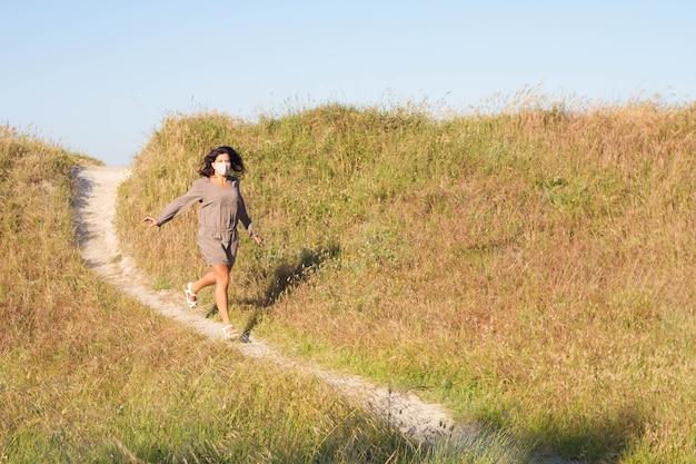Jolie femme d'âge moyen libre et felilz courant le long d'un sentier