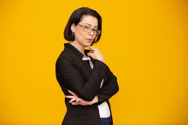 Jolie femme d'âge moyen avec des lunettes et des bras croisés
