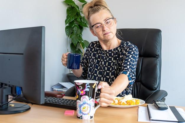 Jolie femme d'âge moyen avec des lunettes à midi au bureau au bureau
