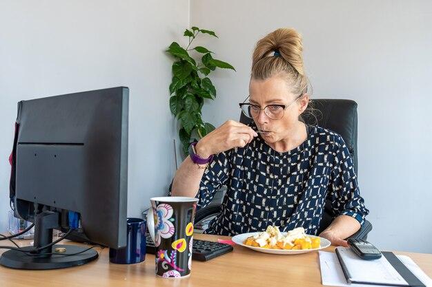 Jolie femme d'âge moyen avec des lunettes en train de déjeuner au bureau sur son lieu de travail