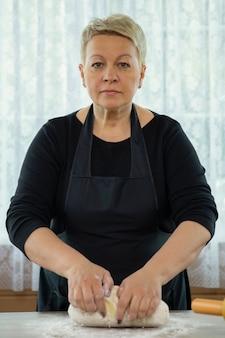 Jolie femme d'âge moyen portant un tablier noir faisant de la pâte de pâtisserie maison dans la cuisine