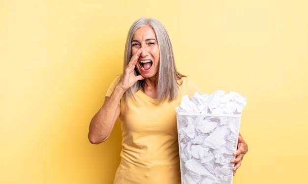 Jolie femme d'âge moyen se sentant heureuse, donnant un grand cri avec les mains à côté de la bouche. concept d'échec des boules de papier