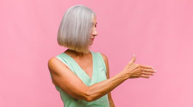 Jolie femme d'âge moyen se sentant heureuse, excitée et positive, donnant un grand cri avec les mains à côté de la bouche, appelant