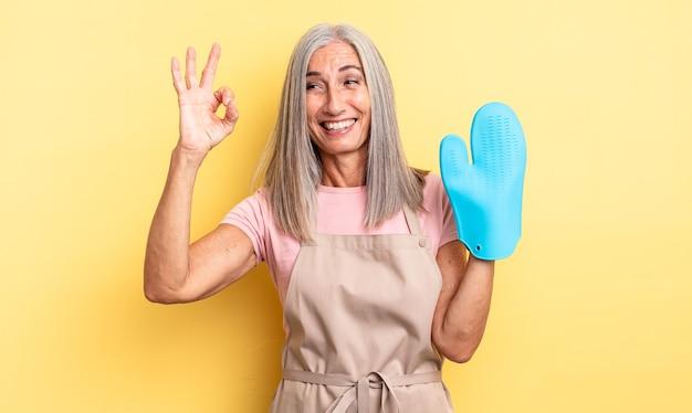 Jolie femme d'âge moyen se sentant heureuse, montrant son approbation avec un geste correct. concept de gants de cuisine