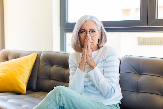 Jolie femme d'âge moyen se sentant inquiète, pleine d'espoir et religieuse, priant fidèlement avec les paumes pressées, implorant pardon