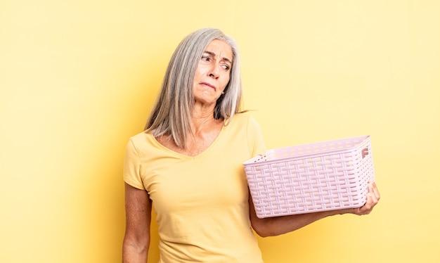 Jolie femme d'âge moyen se sentant triste, contrariée ou en colère et regardant de côté. concept de panier vide