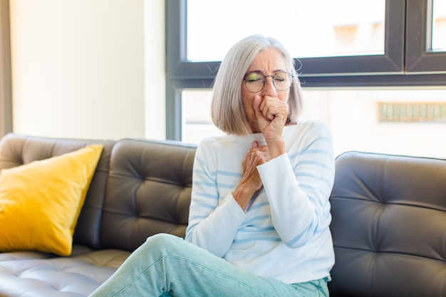 Jolie femme d'âge moyen se sentir malade avec un mal de gorge et des symptômes de grippe, tousser avec la bouche couverte
