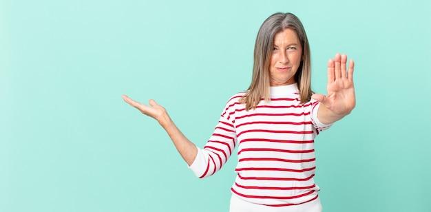 Jolie femme d'âge moyen à la sérieuse montrant la paume ouverte faisant un geste d'arrêt