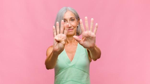 Jolie femme d'âge moyen souriant et à la sympathique, montrant le numéro huit ou huit avec la main en avant, compte à rebours