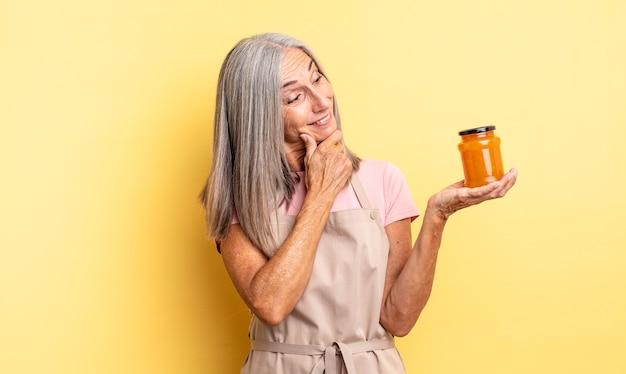 Jolie femme d'âge moyen souriante avec une expression heureuse et confiante avec la main sur le menton. confiture de pêche