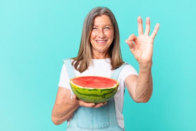 Jolie femme d'âge moyen tenant une tranche de pastèque