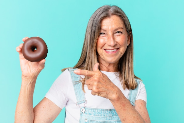 Jolie femme d'âge oisif avec un beignet