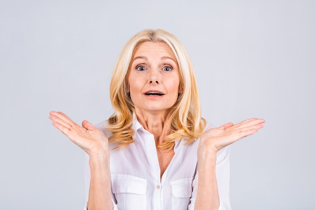 Jolie femme âgée ou d'âge moyen se sentant choquée et excitée, riant, étonnée et heureuse à cause d'une surprise inattendue isolée sur fond blanc.