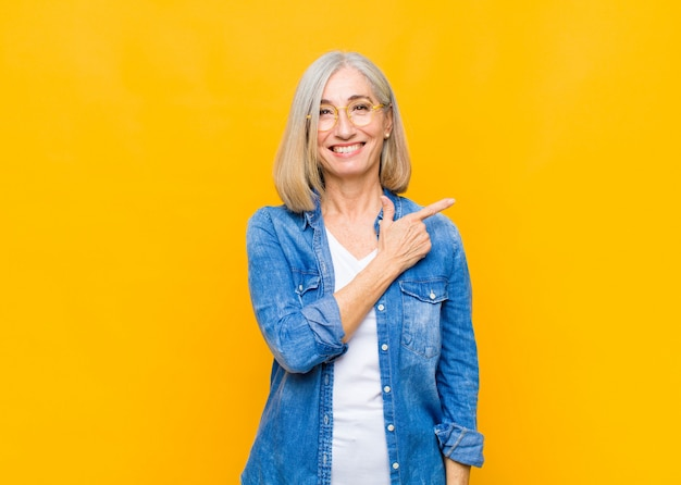 Jolie femme âgée ou d'âge moyen souriant joyeusement, se sentant heureux et pointant vers le côté et vers le haut, montrant l'objet dans l'espace de copie