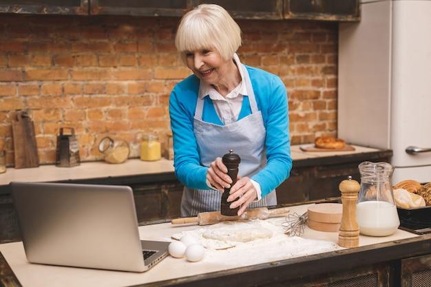 Jolie femme âgée âgée cuisine sur cuisine. grand-mère faisant une pâtisserie savoureuse. à l'aide d'un ordinateur portable.