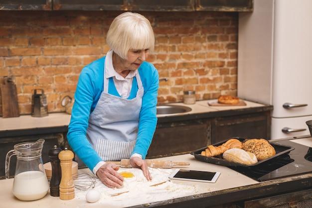 Jolie femme âgée âgée cuisine sur cuisine. grand-mère faisant une pâtisserie savoureuse. à l'aide de la tablette tactile.
